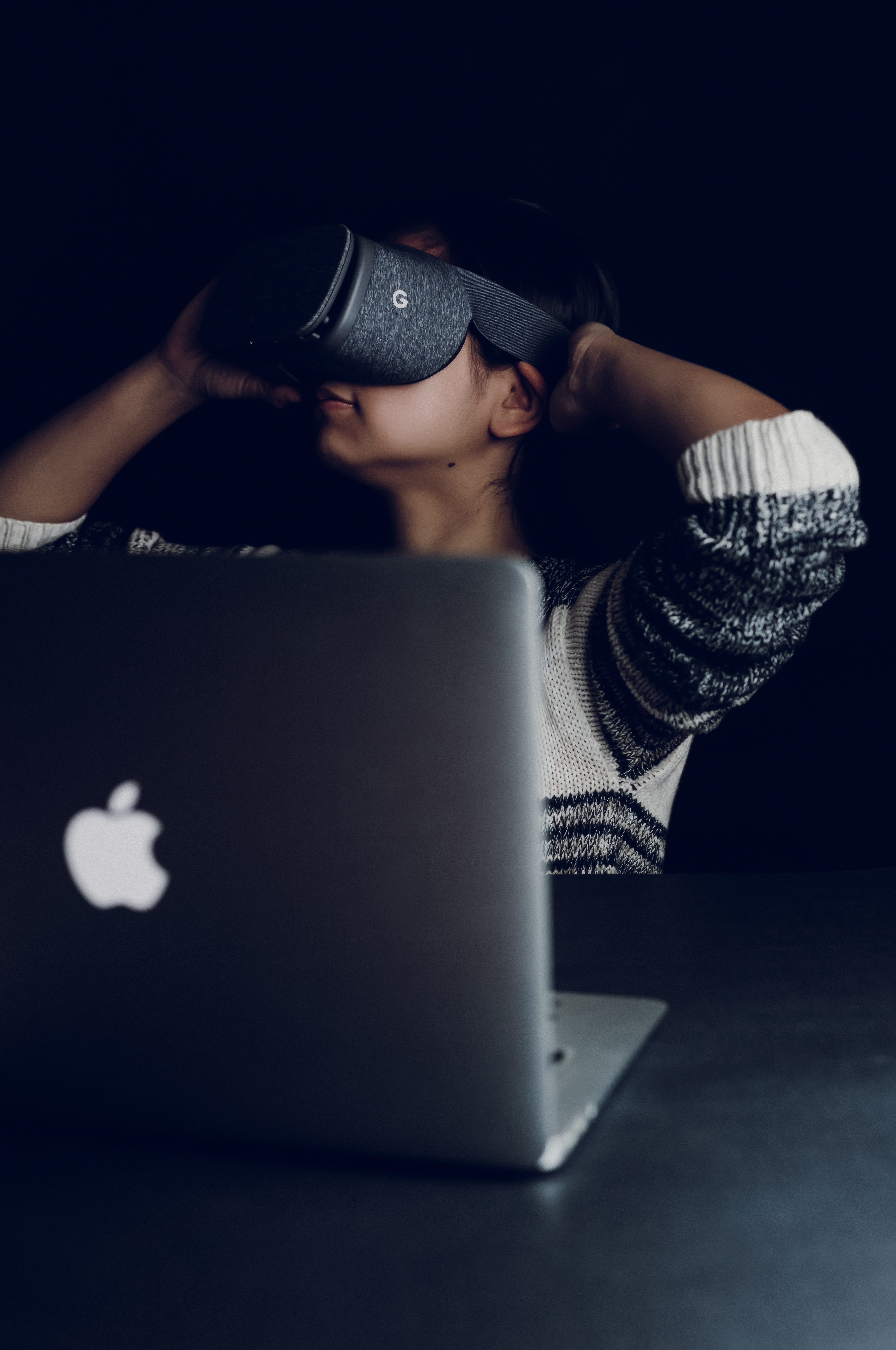 Lady with virtual reality viewer in front of Apple laptop computer.